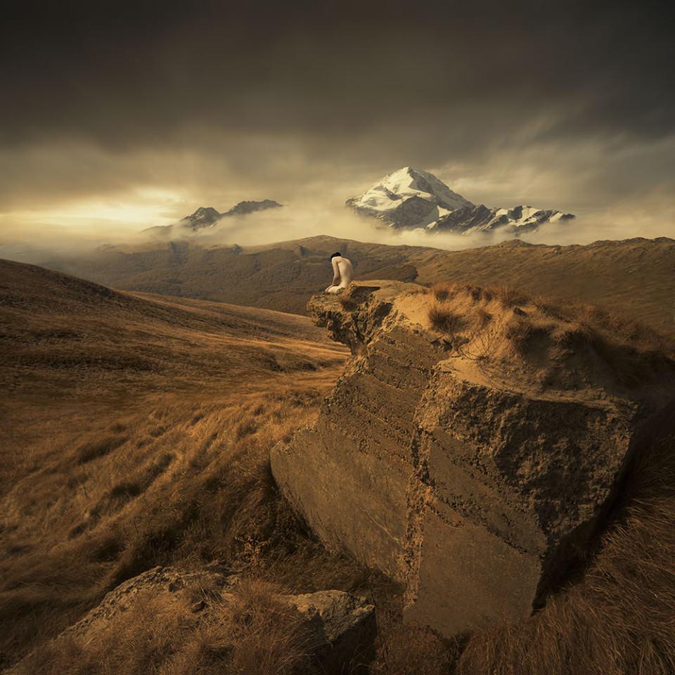 Auf einem Felsvorsprung in einer Steppenlandschaft hockt eine nackte Frau.