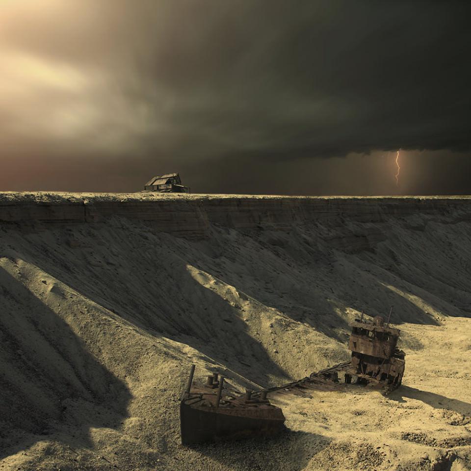 An einem Abhang steht ein Haus, am Fuße des Abhangs liegt ein verrostetes Schiff, halb von Sand bedeckt.