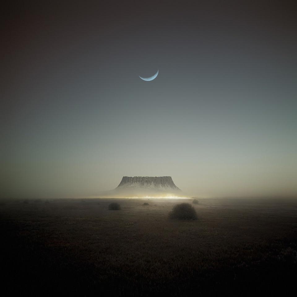 Am Ende einer Steppenlandschaft steht ein Plateau, über dem eine Mondsichel am Himmel steht.