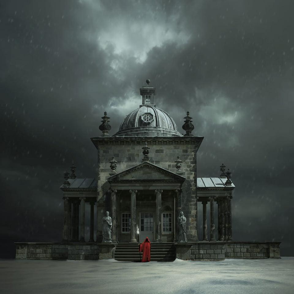 Vor einem Tempel steht ein rot gewandeter Mönch mit einem Fackelstab.
