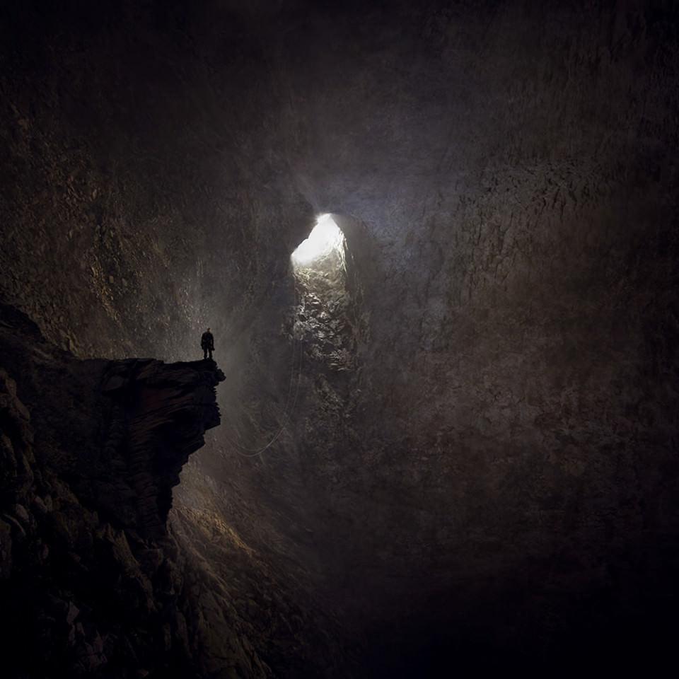 Ein Mensch steht auf einem Felsvorsprung in einer Höhle, in die Licht fällt.