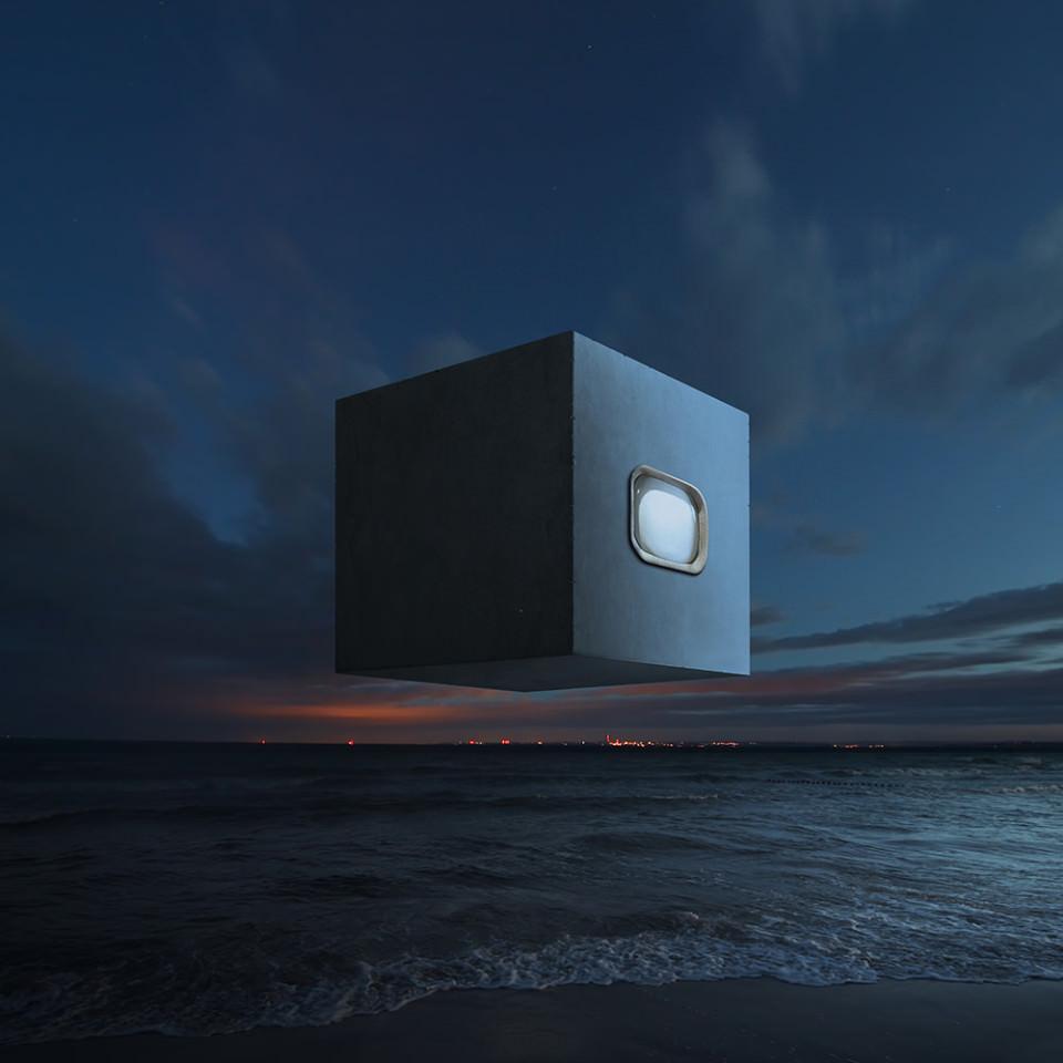 Ein großer, dunkler Kubus mit Fenster schwebt über einem dunklen Strand, am Horizont die Lichter einer Stadt.