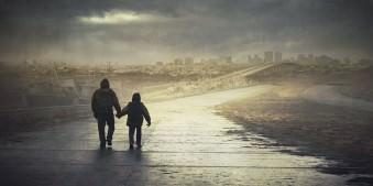 Zwei Menschen laufen eine Straße entlang, die auf eine zerstörte Stadt zuführt.