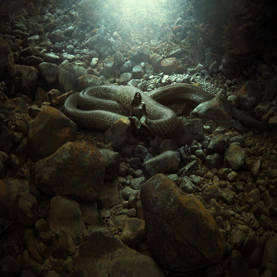 Auf einer Böschung aus großen Steinen liegt eine große Schlange, auf der eine Frau sitzt.