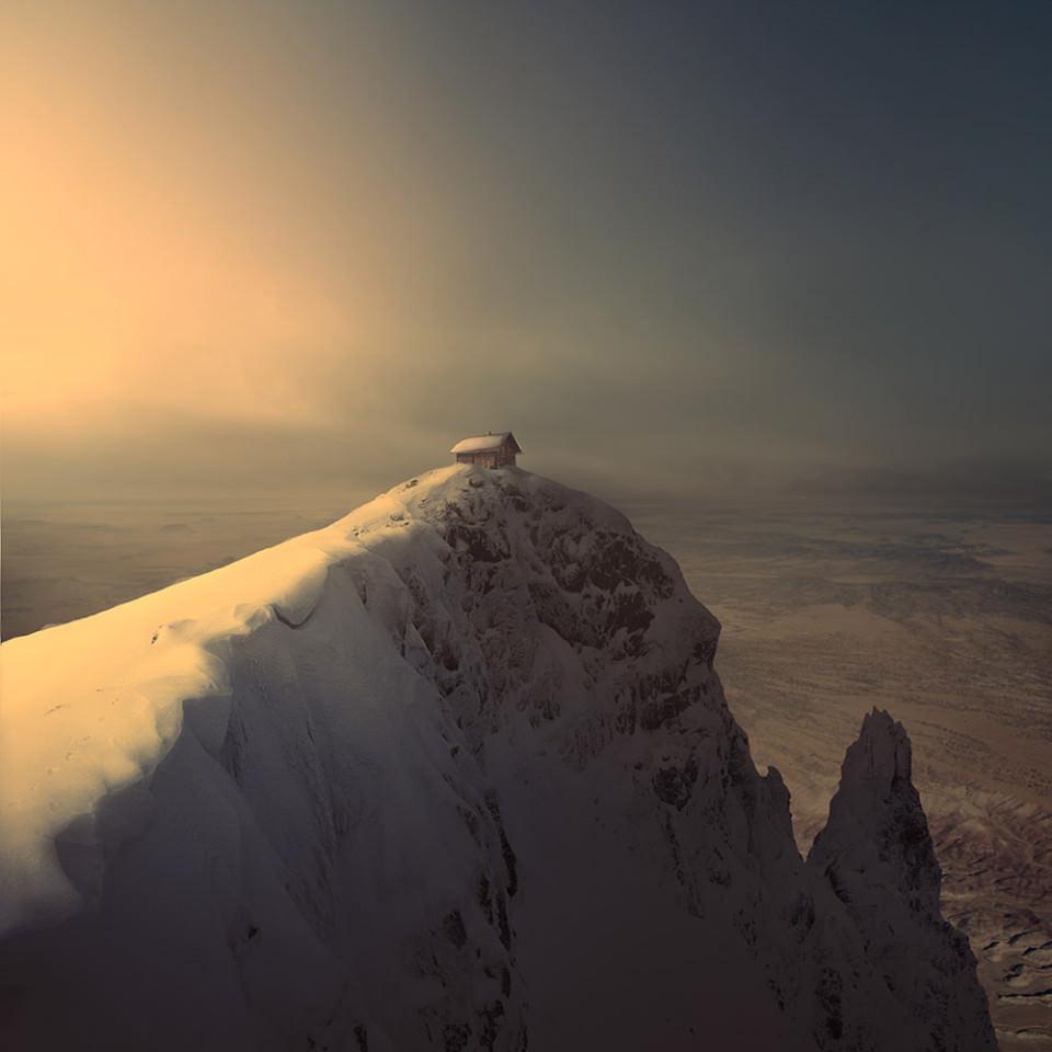 Auf dem Gipfel eines schneebedeckten Gebirges steht eine kleine Hütte.