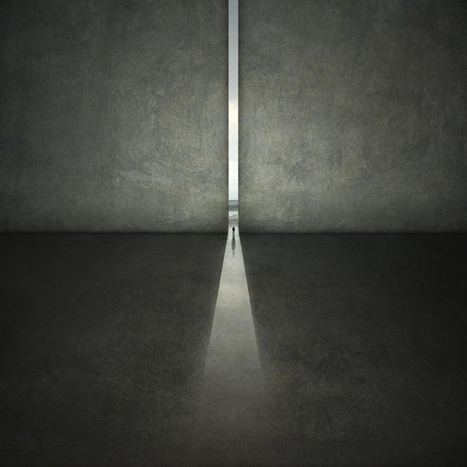 Ein Mensch steht im Spalt einer riesigen Wand, hinter ihm ist Meer zu sehen.