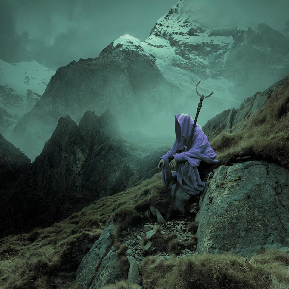 Eine Gestalt in violettem Umhang sitzt mit einem Stab auf einem Felsen vor einer Berglandschaft.