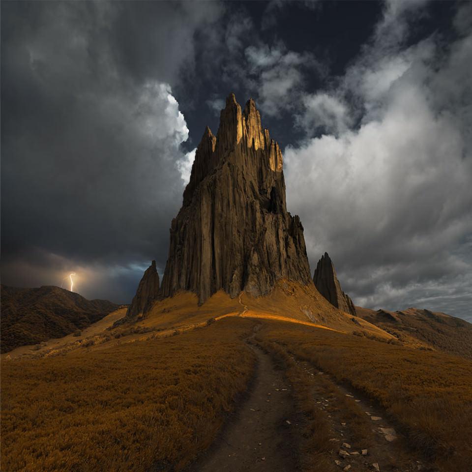 Ein hoher Felsen ragt steil aus einer Steppenlandschaft auf.