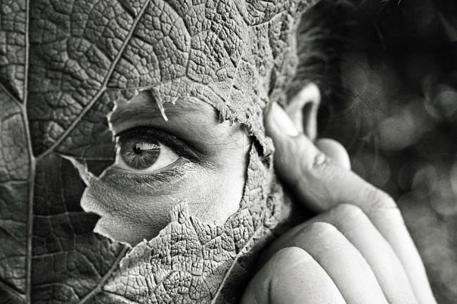 Ein Mensch mit Blatt vor dem Gesicht