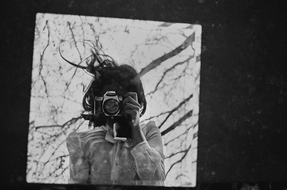 Ein Selbstportrait einer Frau mit Kamera im Spiegel.