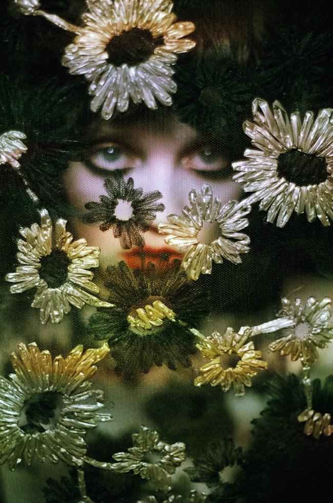 Das Gesicht einer Frau hinter einem Netzstoff, bestickt mit Blumen.