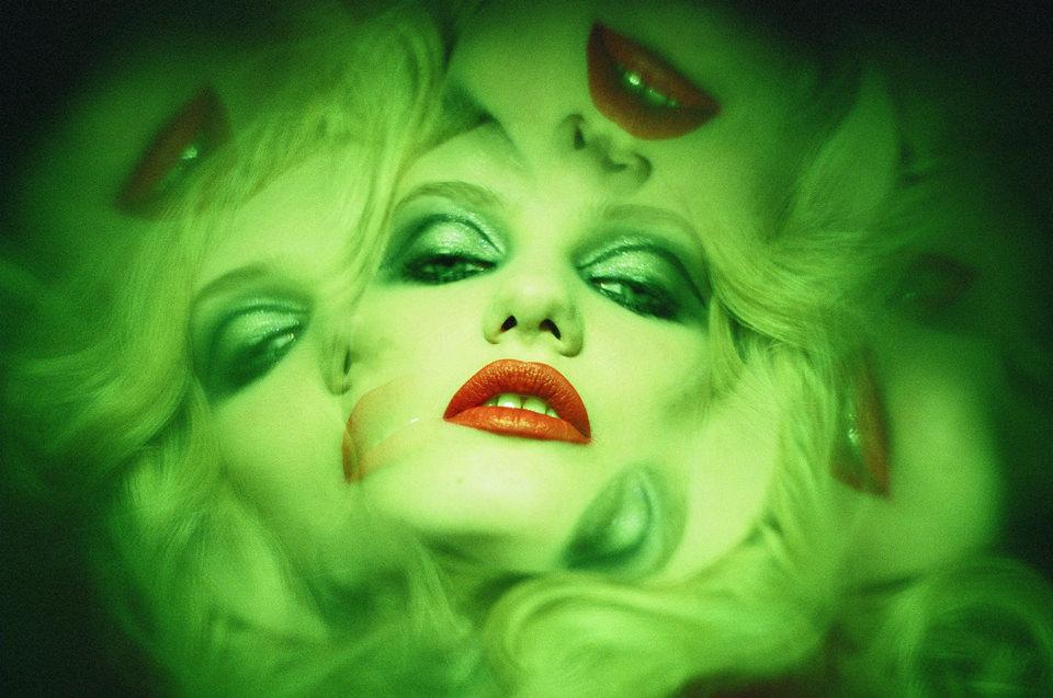 Ein grünes Frauengesicht mit Spiegelungen.