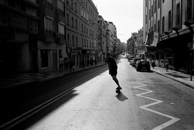 Ein Skater cruist schräg durch die Straße.