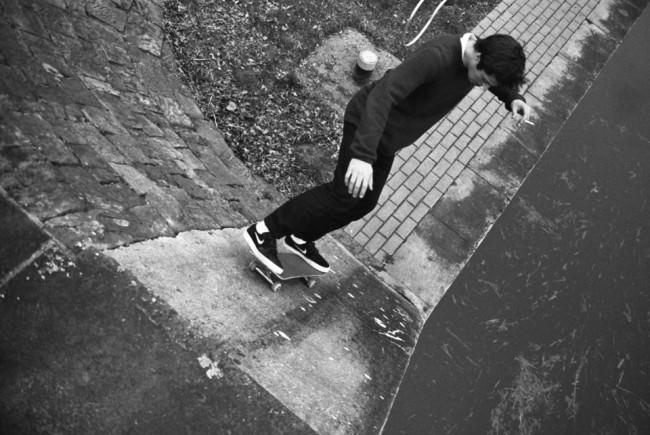 Skater auf einer Flutmauer, neben ihm das Meer.