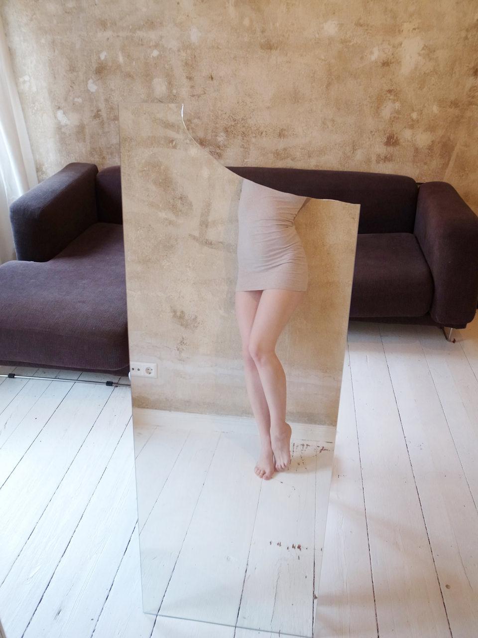 Frau ohne Kopf und ein Spiegel mit einer hübschen Wand.