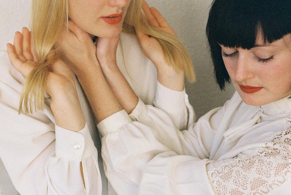 Zwei Frauen, eine blond, die andere mit schwarzen Haaren, berühren sich.