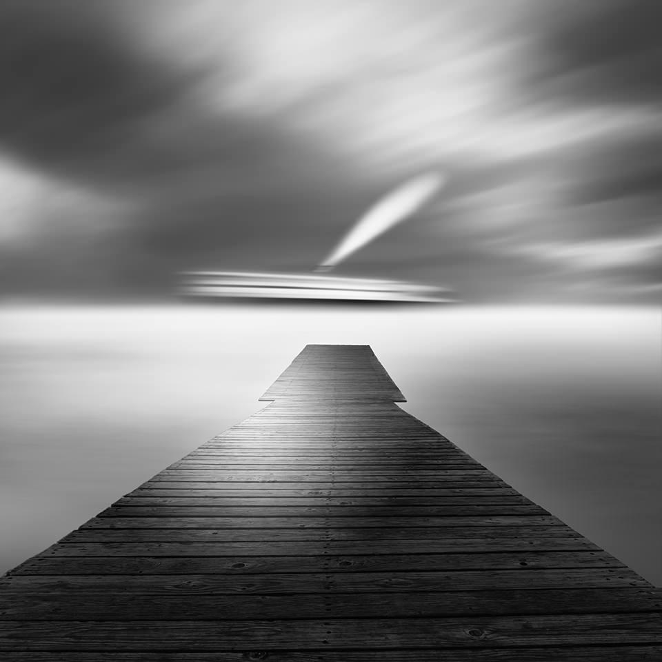 Ein Steg führt ins Meer. Am Horizont ist unscharf ein Schiff zu sehen.