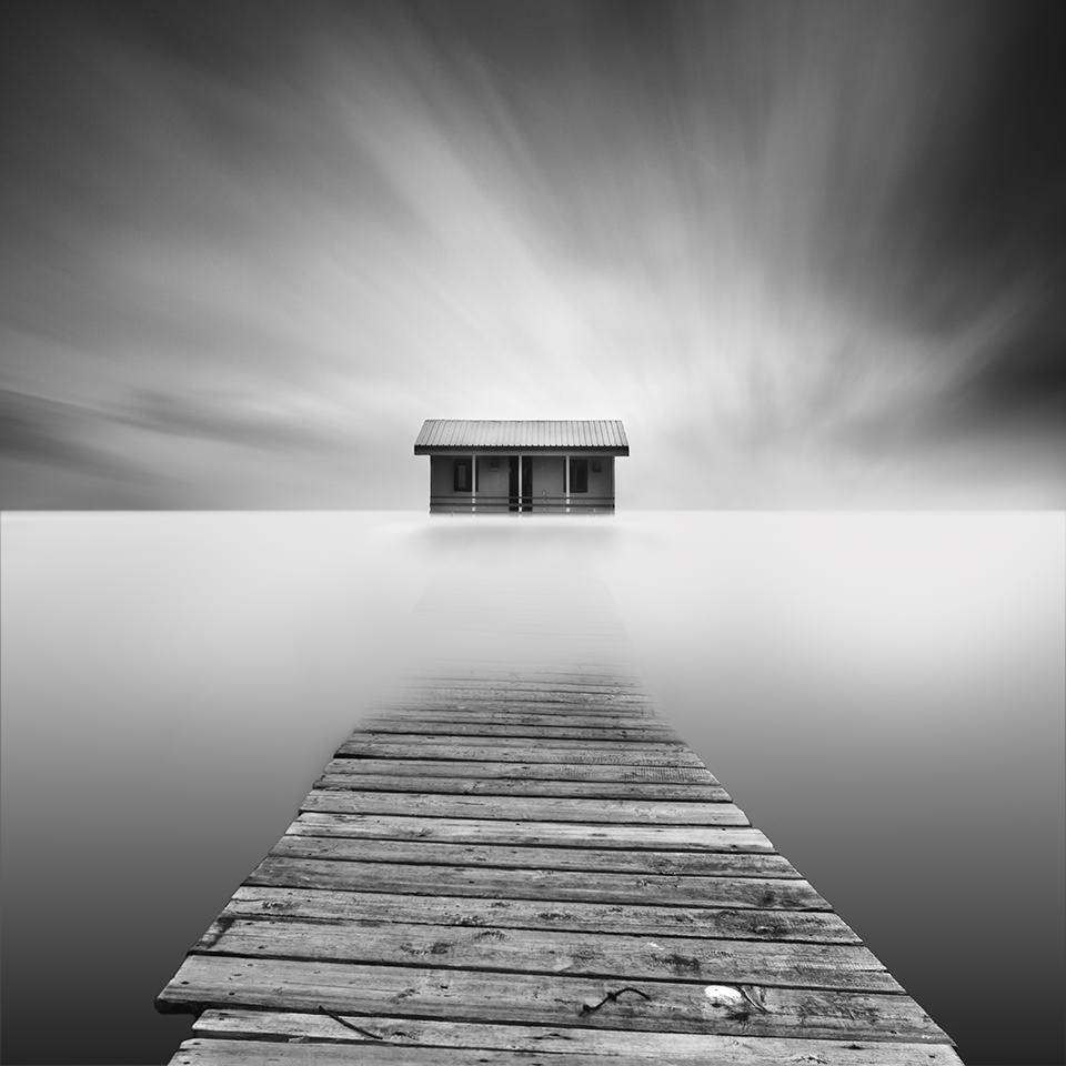 Ein Steg führt ins Meer. Am Horizont ein Haus.