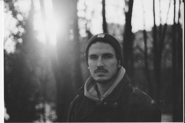 junger Mann vor Bäumen im Abendlicht