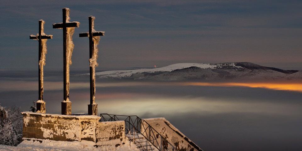Eine Bergspitze mit drei Gipfelkreuzen trohnt über einem Wolkenmeer.