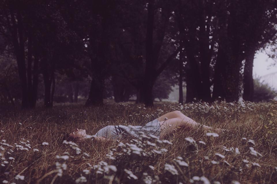Portrait: Eine Frau liegt vor einem Wald im Feld.