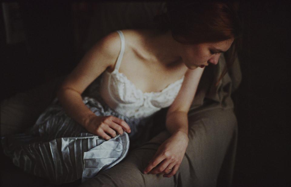 Portrait: Eine Frau sitzt im Unterhemd auf einem Sessel.
