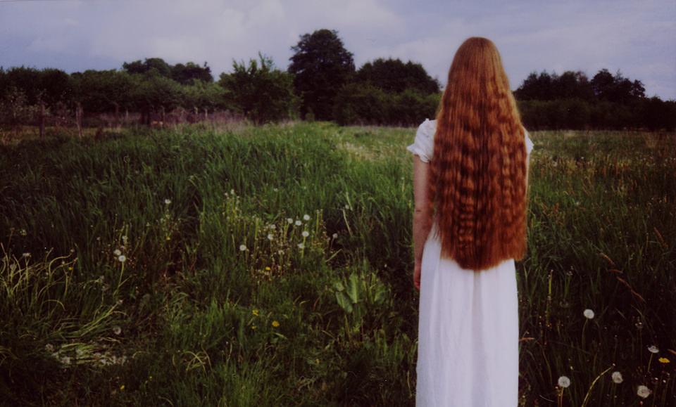 Portrait: Eine Frau mit roten Locken steht vor einem Feld.
