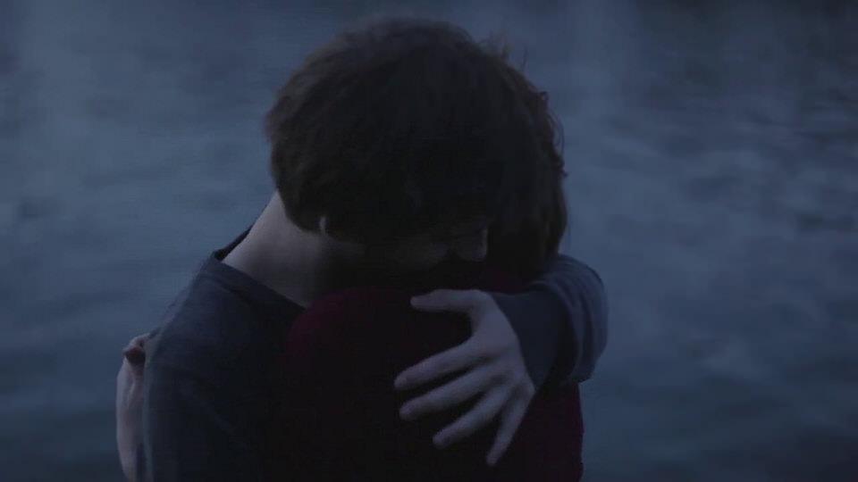 Portrait: Ein Paar steht bei schwachem Licht abends am Ufer.