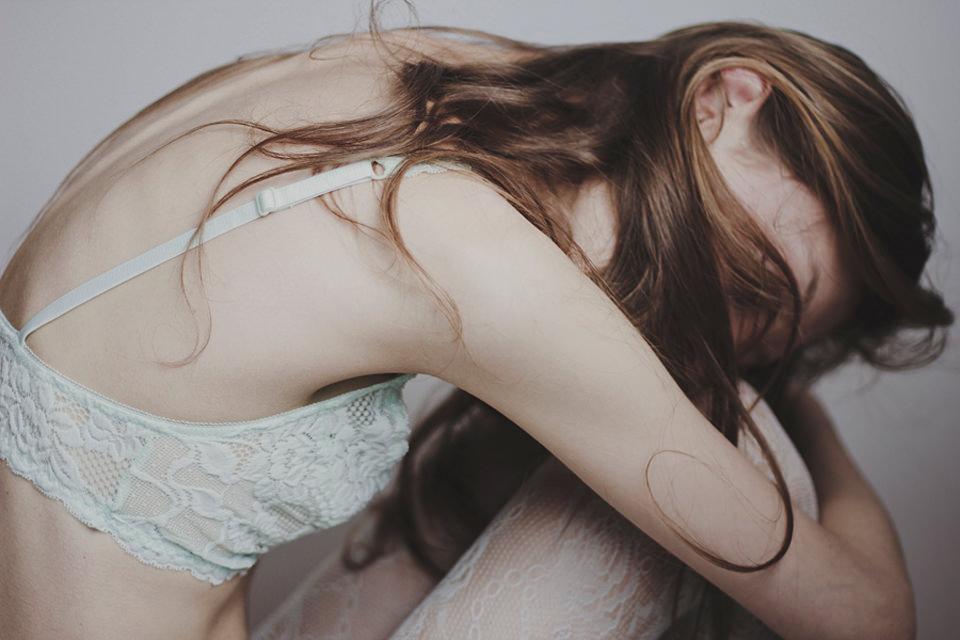 Portrait: Eine Frau sitzt und beugt sich auf ihre Knie.