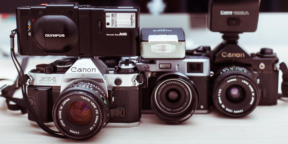 Aufgereihte Kameras auf einem Schreibtisch.