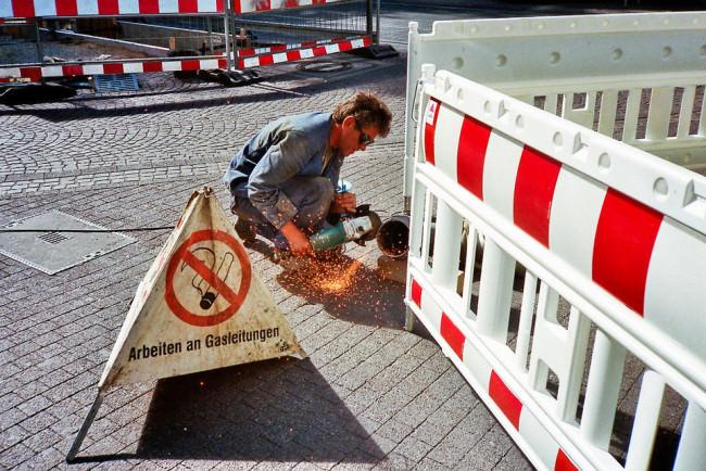 Ein Bauarbeiter sägt an einem Rohr.