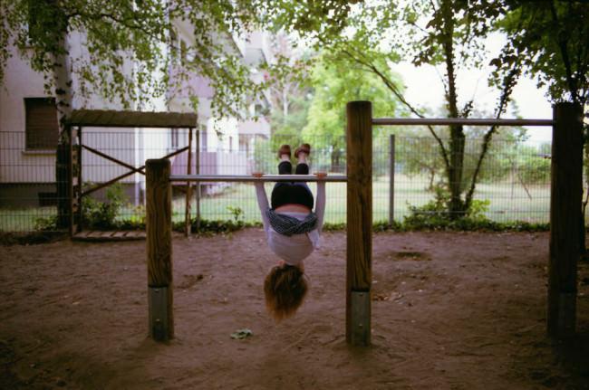 Ein Kind turnt an einer Stange.