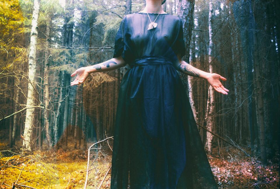 Frau im Wald, die ihre Arme ausstreckt.