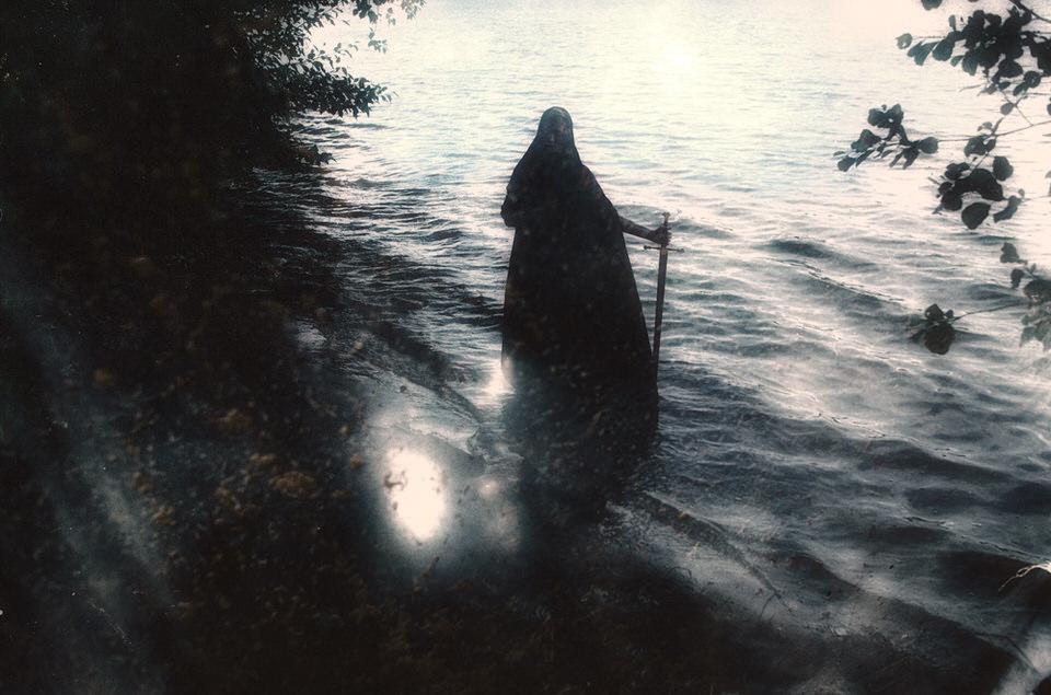 Doppelbelichtung: Eine Person mit Schwert in der Hand steht am Wasser.