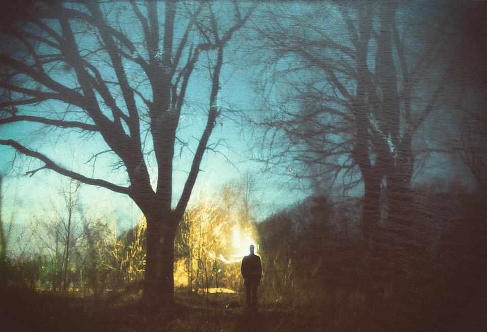Doppelbelichtung mit einer Person, die vor einer Licht- oder Feuerquelle steht.