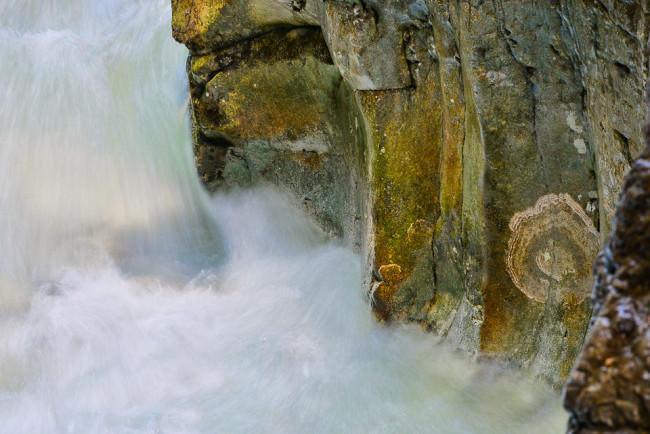 Landschaftsfotografie: Wasser fließt an hohen Steinen vorbei, Detailaufnahme.