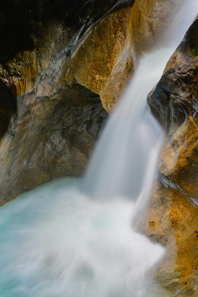Landschaftsfotografie: Ein Mini-Wasserfall stürzt an Steinen hinab.