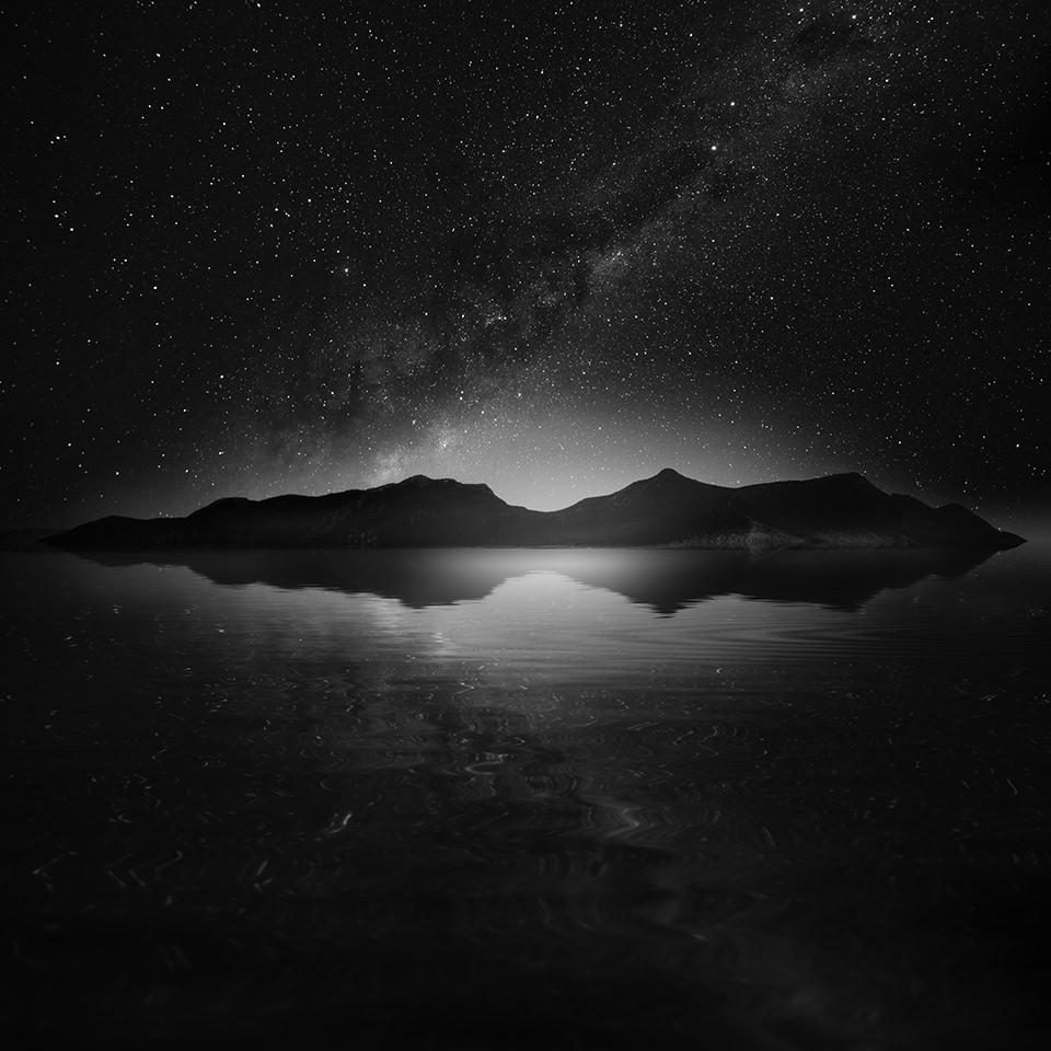 Eine Insel im Meer, darüber der Sternenhimmel.