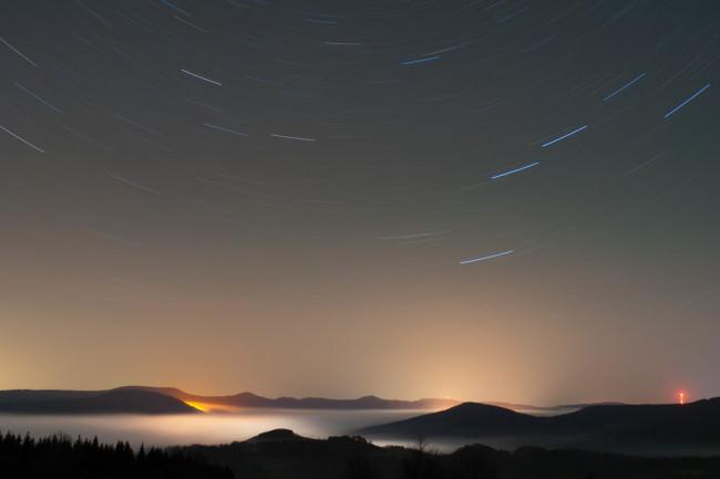 Eine Langzeitaufnahme von Sternen über einem nebelverhangenen Gebirge.