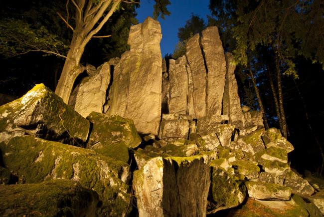Eine Wand aus Steinen in der Nacht, beleuchtet.