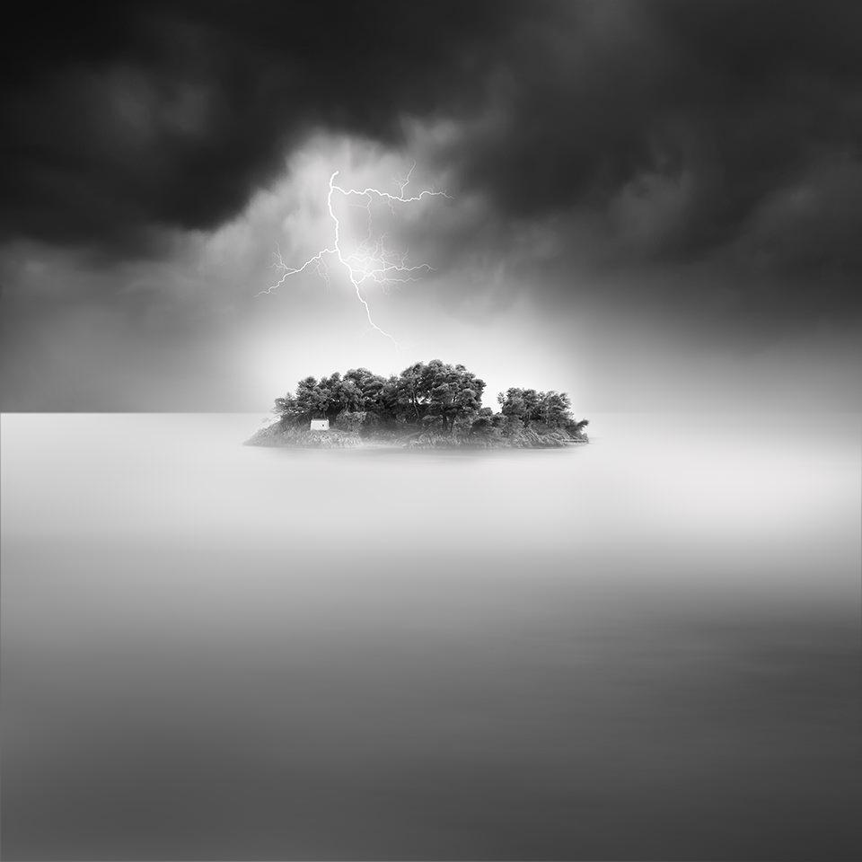 Eine Insel im Meer. Darüber Gewitterwolken und ein Blitz.