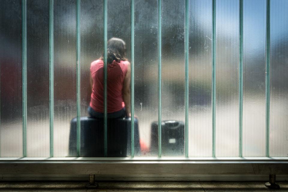 Eine Frau lehnt sich an eine Scheibe an und wartet.