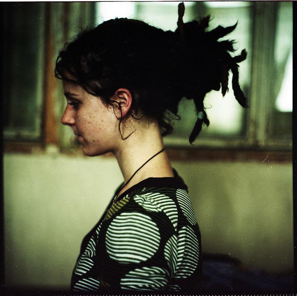 Ein Mädchen mit Dreadlocks seitlich fotografiert