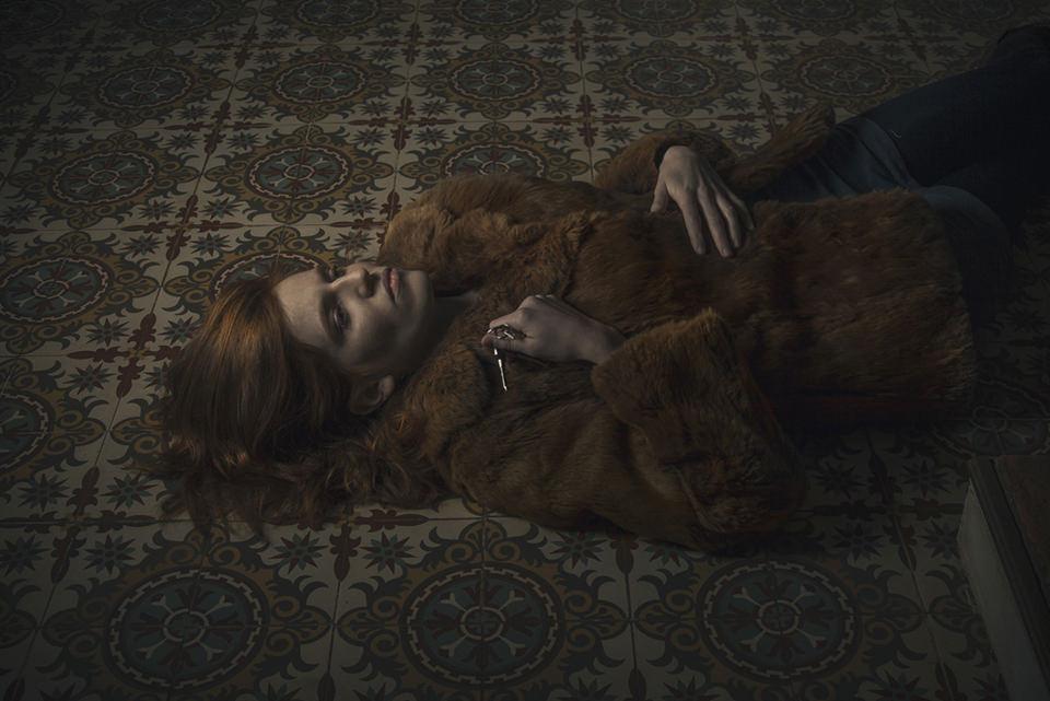 Eine Frau liegt in einem Pelzmantel auf dem Boden