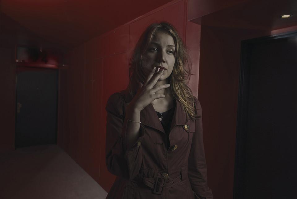 Eine Frau rauchend in einem Hausflur