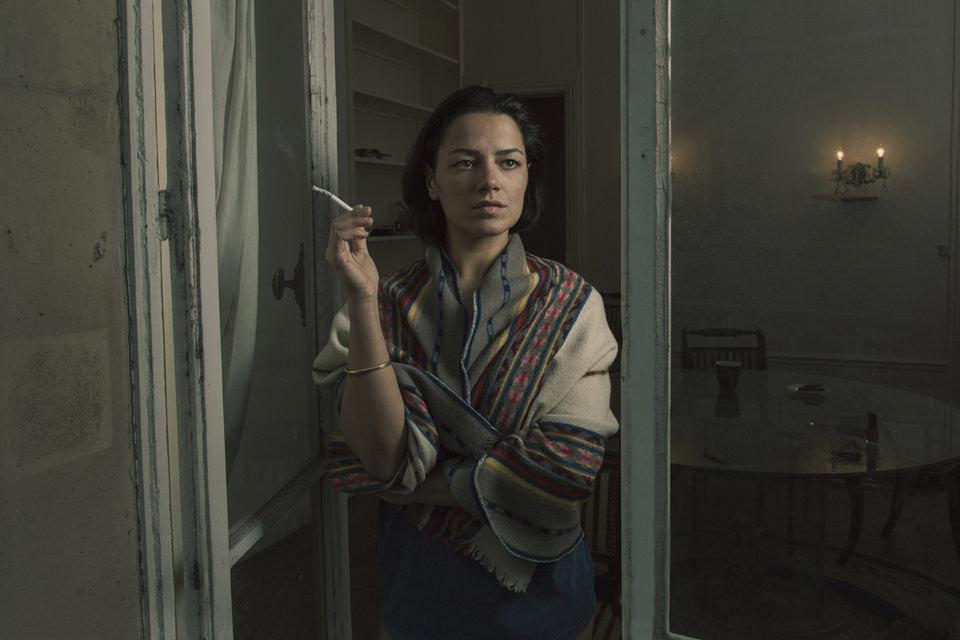 Eine Frau steht rauchend in einer Tür
