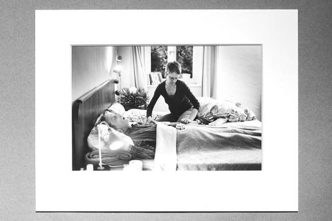Die Frau rückt die Bettdecke zurecht und schaut dabei nicht zu ihrem Mann.