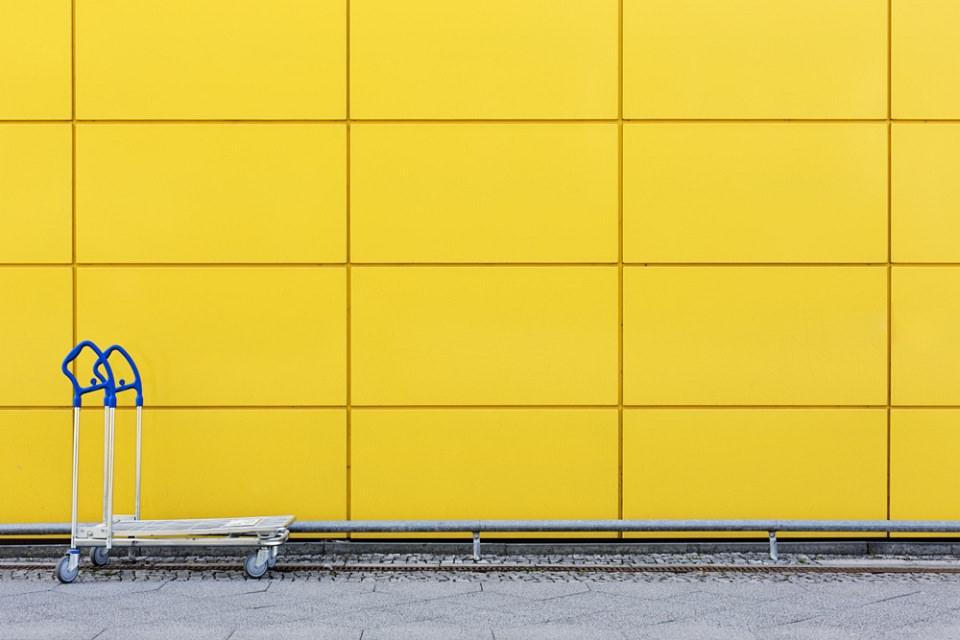 Einkaufswagen mit blauen Griffen vor einer gelben Wand.