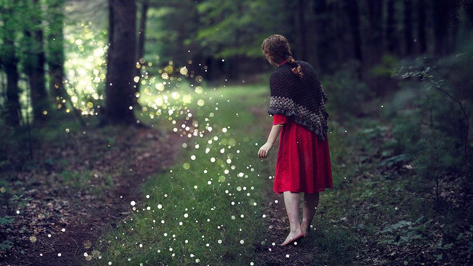 Eine Frau im roten Kleid folgt seltsamen Lichtern im Wald.