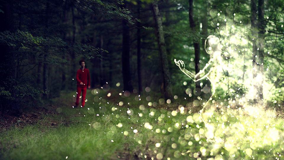 Eine Lichtgestalt lockt einen Mann im roten Anzug in den Wald.